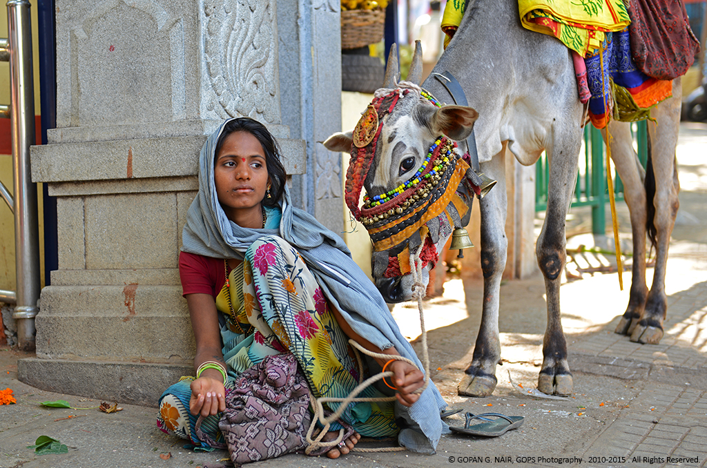 """Kole Basava"" with a gypsy girl seeking alms in front of a temple."