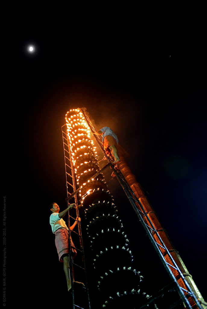 LIGHTING THE DEEPA STHAMBHA (OIL LAMP PILLAR) AT THE ENTRANCE OF THE TEMPLE