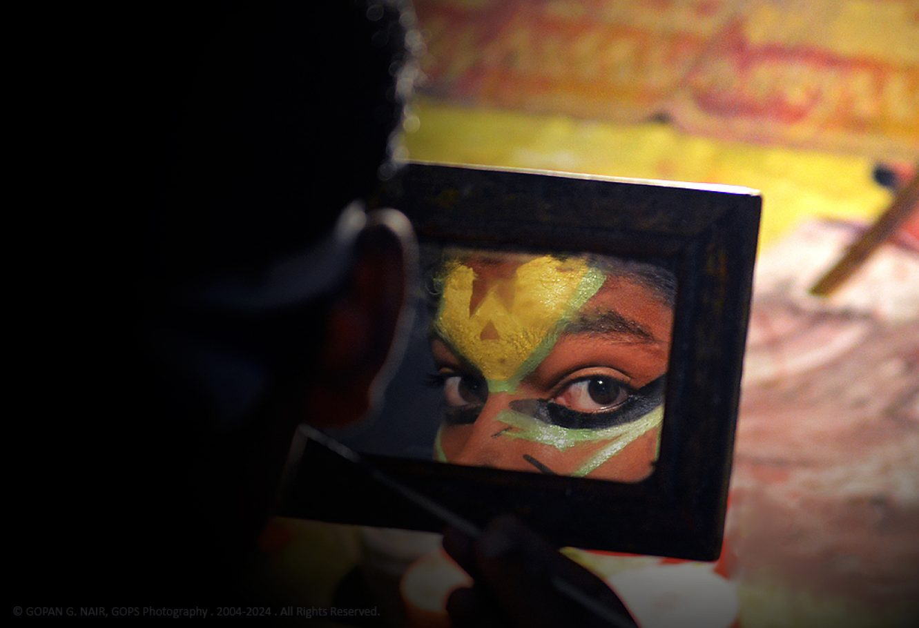 A KATHAKALI PERFORMER APPLYING MAKEUP